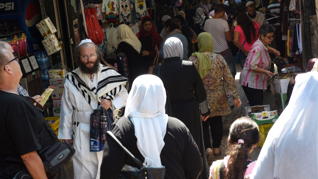 An Ultra-Orthodox Jew wears and white robe and prayer shawl while walking between Muslim women in the Old City of Jerusalem, on Rosh HaShanah, the Jewish New Year, and the Islamic New Year, September 21, 2017. Both religions follow the lunar calendar.