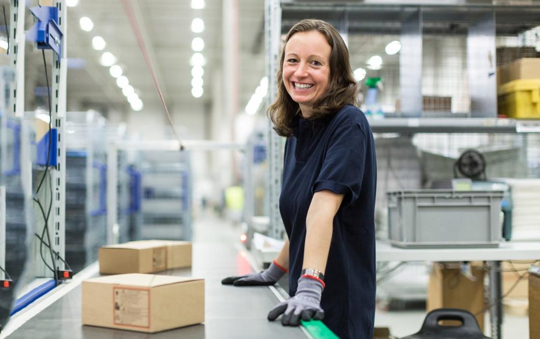 Ein Frau steht in einer großen Halle an einem Förderband. Sie arbeitet für einen Versandhandel.