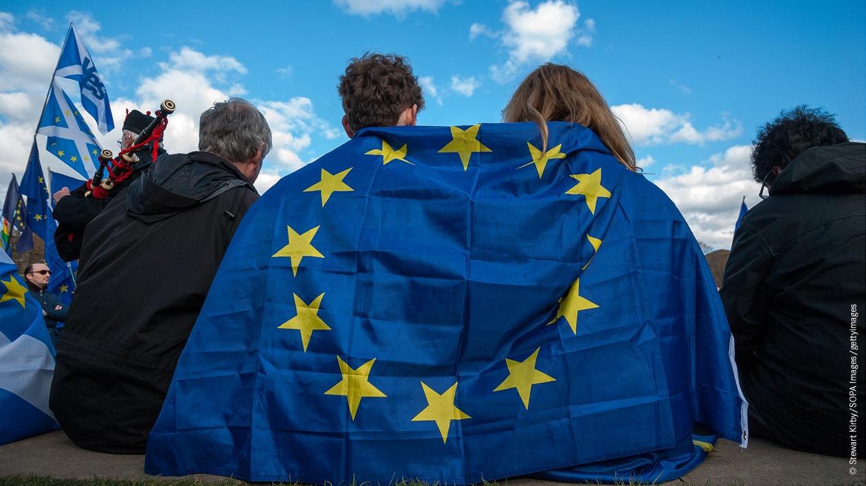 Zwei junge Demonstranten protestieren mit der EU-Fahne um die Schultern gelegt vor dem Schottischen Parlament ind Edinburgh