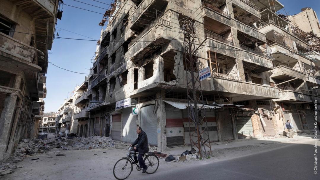 Straßenszene des durch Kampfhandlungen zwischen Rebellengruppen und Regierungstruppen zerstörtem Stadtteil im syrischen Homs