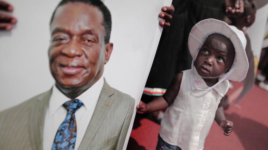 Ein kleines Mädchen blickt fragend auf das Foto des neuen Präsidenten Emmerson Mnangagwa