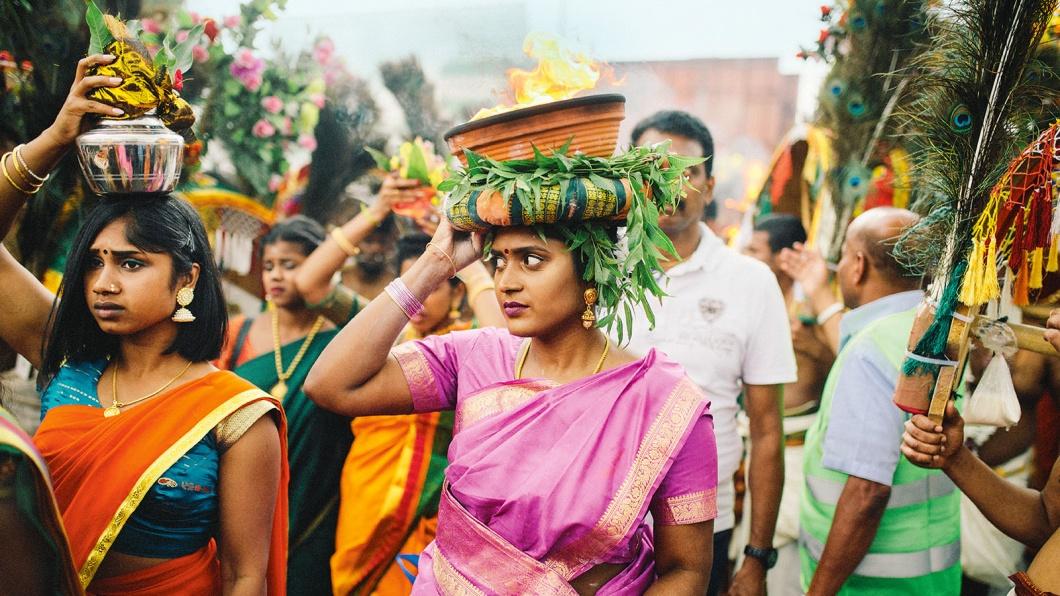"""Beim Wagenfest """"Theer"""" trägt eine junge Frau eine Feuerschale um den Tempel"""