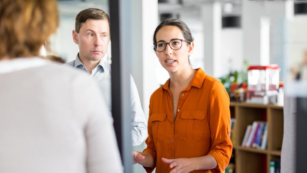Gesprächssituation mit drei Personen in einem Büroraum