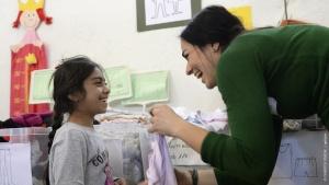 """Ein Mädchen aus Syrien und eine Helferin in der Flüchtlingsunterkunft """"Bayernkaserne"""" in München lachen sich an"""