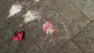Kinderzeichnung mit Kreide auf Straße.