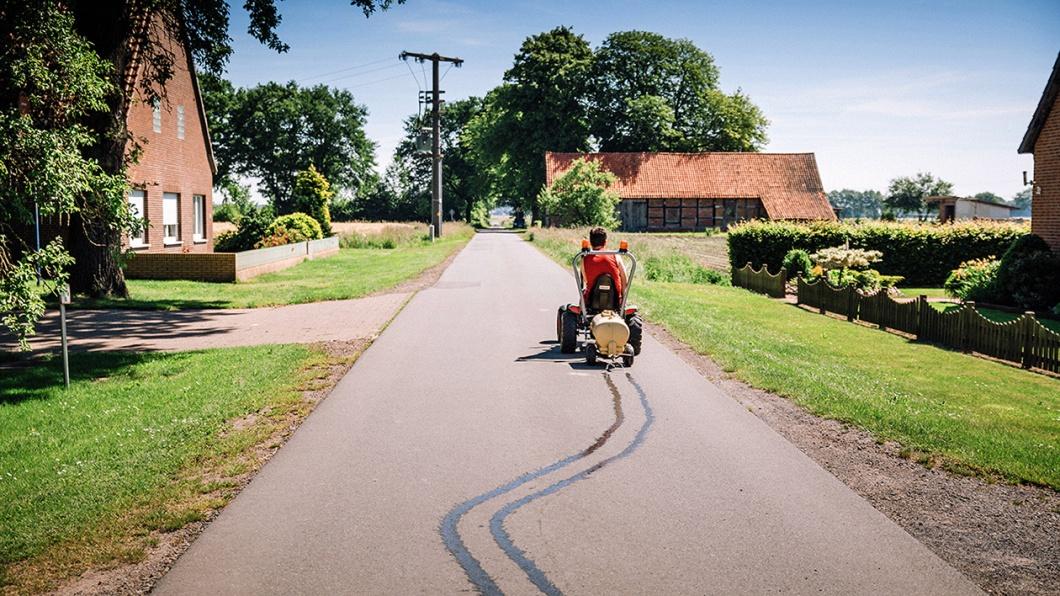 Mit dem selbstgebauten Güllewagen für sein Kettcar spielt Marvin Landwirt und wässert die Straße vor dem Hof seiner Eltern