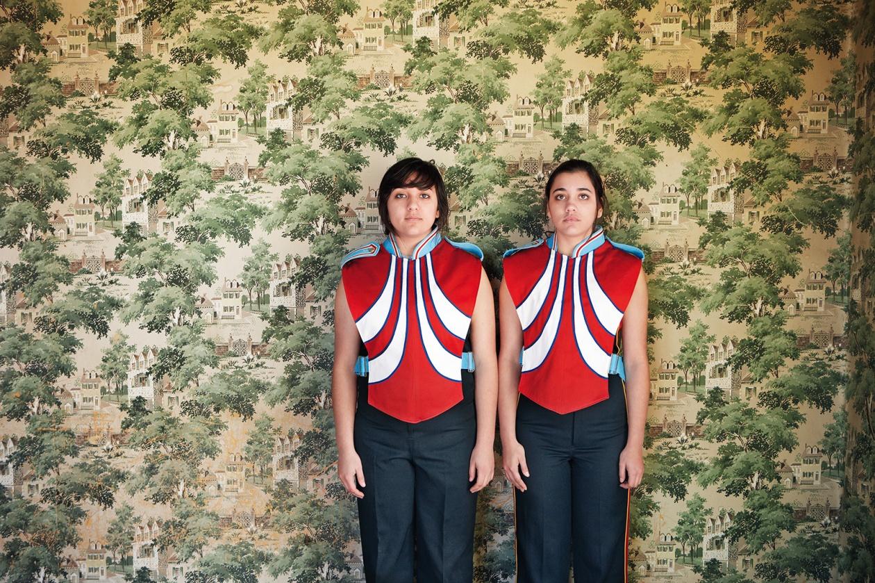 Zwei Schwestern in Marfa, Texas tragen die Uniform einer Blaskapelle und stehen vor eine opulenten Tapete