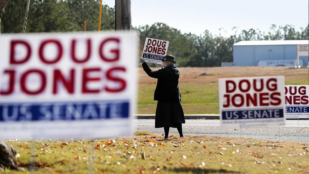 Eine Anhängerin des Demokraten Doug Jones hält aam Straßenrand ein Schild mit der Aufschrift Doug Jones für den US Senat nach oben.
