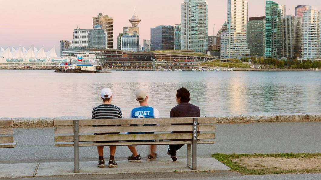Menschen sitzen auf einer Bank vor der Skyline von Vancouver