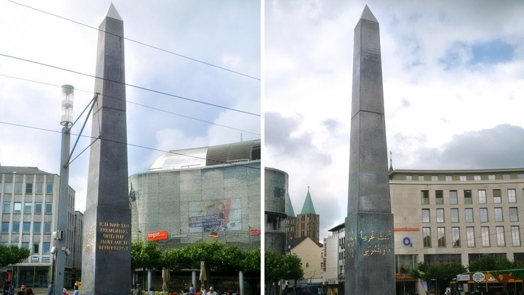 """Flüchtlingskunst in Kassel: Olu Oguibes Obelisk auf dem Königsplatz. Auf Deutsch, Arabisch, Englisch und Türkisch steht dort geschrieben: """"Ich war ein Fremdling, und ihr habt mich beherbergt."""""""