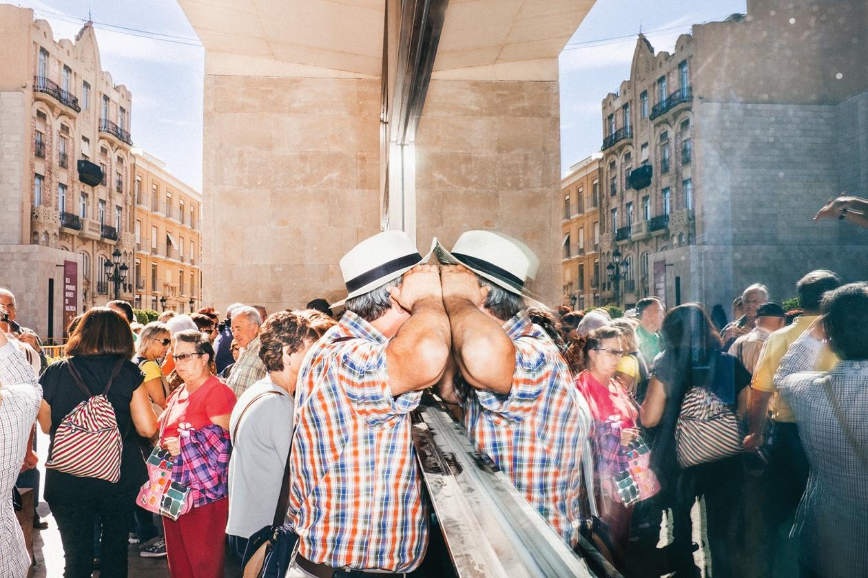 Ein Mann einer Touristengruppe schaut durch eine Scheibe auf dem Plaça de Dècim Juni Brut. Spanien, Valencia, 24. Oktober 2014