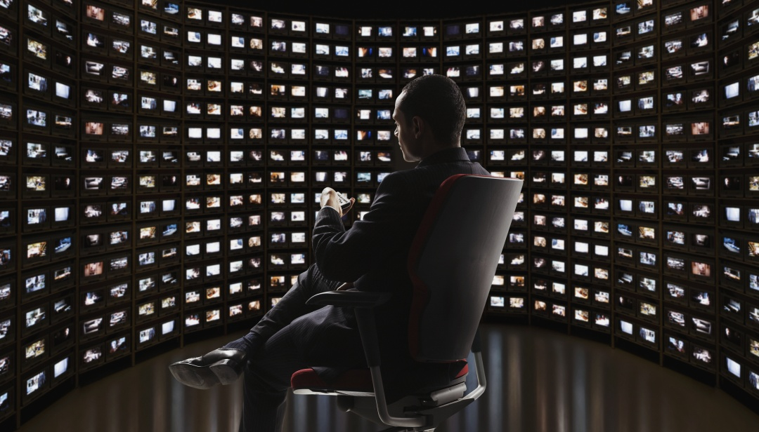 Symbolbild Mann vor vielen Monitoren