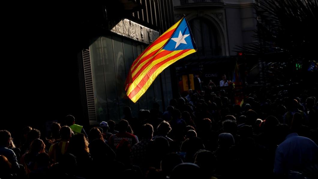 People walk through a street as an Estelada (Catalan separatist flag) flutters in Barcelona