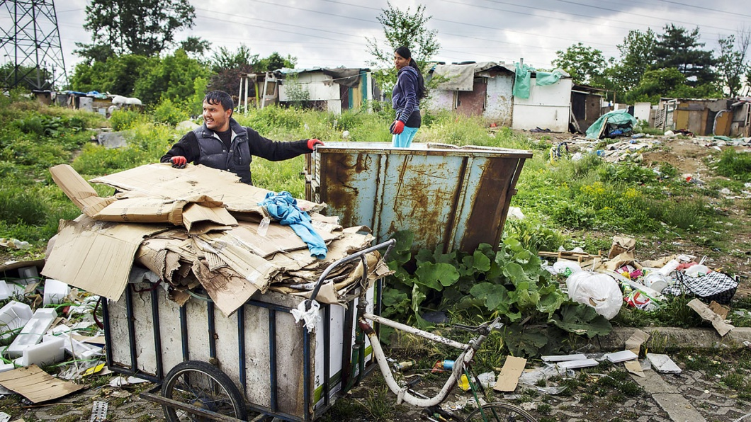 Ein Mann lädt am 28. Mai 2015 Pappe von einem selbstgebauten Fahrrad in einen Container am Rande einer Romasiedlung in Belgrad.