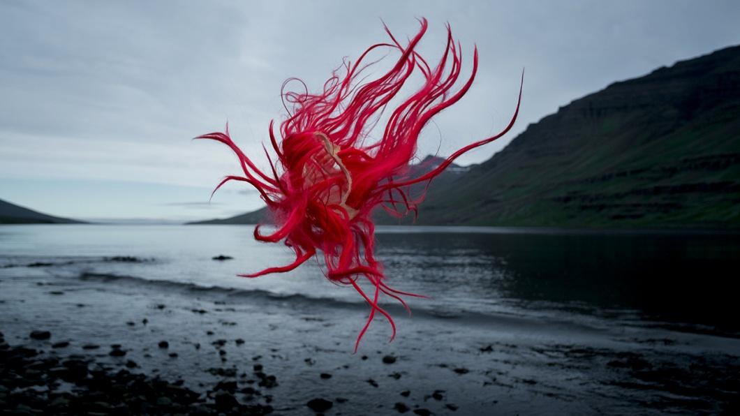 Perücke mit roten Haaren schwebt durch mystische Küstenlandschaft in Norwegen