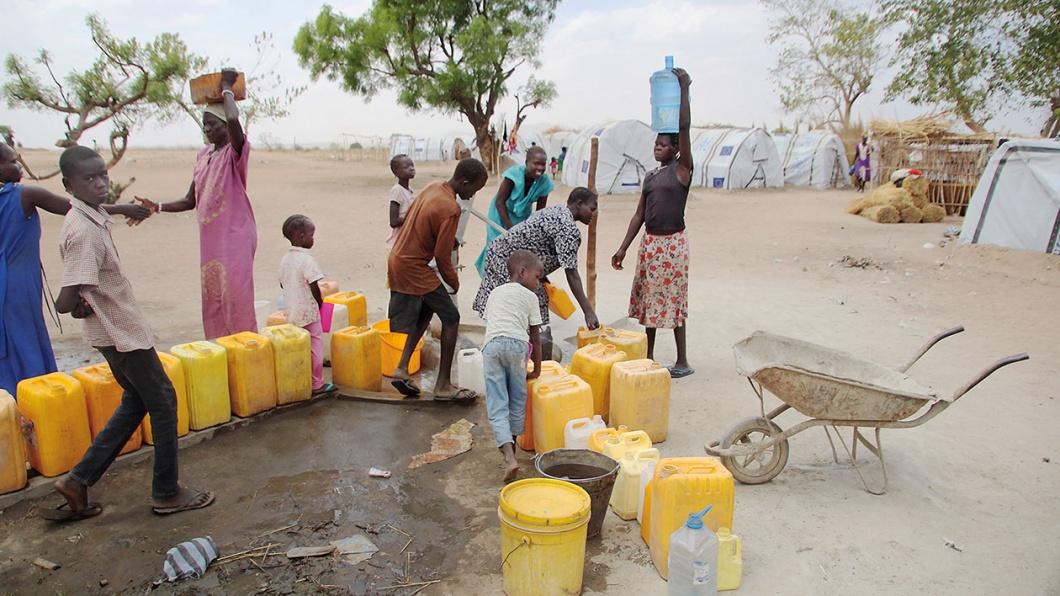Menschen an der Wasserpumpe im Flüchtlingscamp Gumbo im Südsudan
