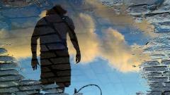 Ein Mann spiegelt sich in einer Pfütze auf der Straße.