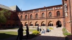 Menschen sitzen im Innenhof des Dom zu Riga.