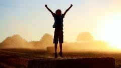 Ein Junge springt in der Abendsonne mit hochgestreckten Armen auf einem Strohballen.