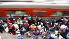 Menschen warten am Bahnhof auf einen einfahrenden Zug.