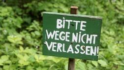 """Schild mit der Aufschrift """"Bitte Wege nicht verlassen!"""" im Freien."""