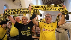 BVB-Fans schwenken BVB-Schals bei einem ökumenischen Gottesdienst in der Dreifaltigkeitskirche in Dortmund zu Beginn der neuen Saison von Borussia Dortmund.