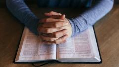 Gefaltete Hände über einer aufgeschlagenen Bibel.