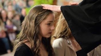 Pfarrer segnet zwei Mädchen bei einem Konfirmationsgottesdienst in der Michaeliskirche in Leipzig-Gohlis.