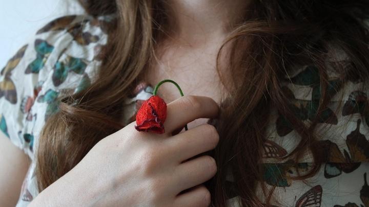 Nahaufnahme einer Frau, die eine vertrocknete Rose in den Händen hält.