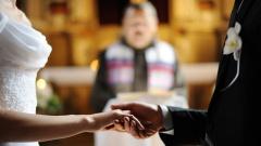 Brautpaar steht in einer Kirche vor dem Altar.