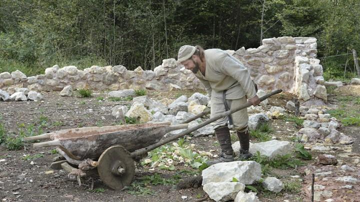 In einem mittelalterlichen Gewand schiebt Steinmetz Jens Lautenschlager auf der Baustelle des Campus Galli, bei Messkirch eine mittelalterliche Schubkarre.