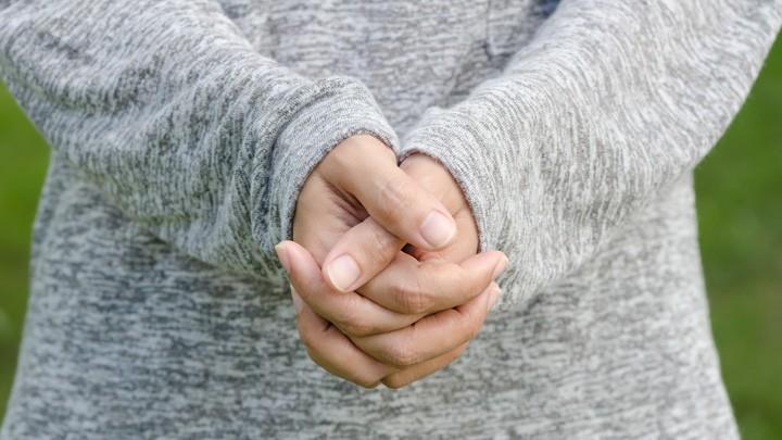 Zum Gebet gefaltete Hände einer jungen Frau.