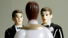 Zwei männliche Figuren vor einem Pastor.