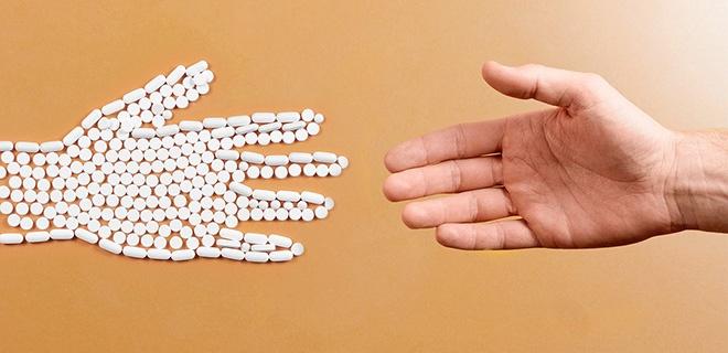 Fotomontge: Zwei Hände entegegengestreckt. Eine ist echt, die andere aus Tabletten und Pillen und erinnert an ein Skelett.