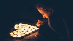 Junge Frau zündet Teelichter in Form eines Herzens an.