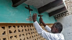 Ein Mann schlägt das Kreuz über seiner Haustür ab, nachdem er vom zum Christentum zum Hinduismus konvertiert ist.
