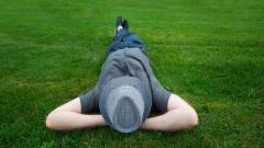 Ein Mann liegt entspannt auf einer grünen Wiese.