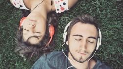 Mann und Frau liegen auf einer Wiese und hören über Kopfhörer Musik.