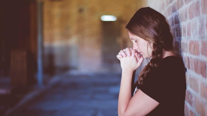 Eine junge Frau lehnt mit dem Rücken an einer Backsteinwand und betet.