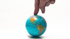 Finger auf kleiner Weltkugel