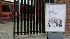 """Foto zeigt den Eingangsbereich zur Tagung """"Familie von morgen"""", die im April 2017 in Berlin stattfand. Zu sehen ist ein Aufsteller mit dem Tagungsplakat vor dem geöffneten Eingangstor."""