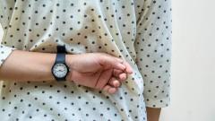 Eine Frau hält ihren Arm mit Armbanduhr hinter ihrem Rücken versteckt.