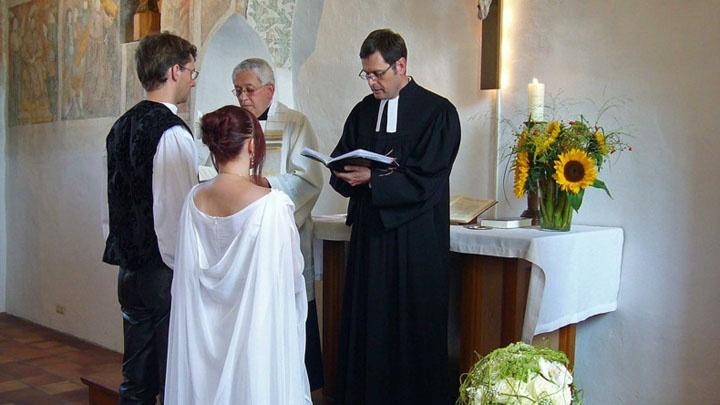 Brautpaar steht in einer Kirche vor zwei Pfarrern.