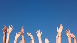 In die Höhe gestreckte Arme sind vor blauem Himmel zu sehen.