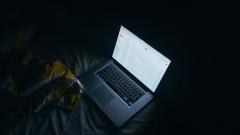 Der Bildschirm eines Laptops leuchtet auf einem Bett in einem dunklen Arbeitszimmer.