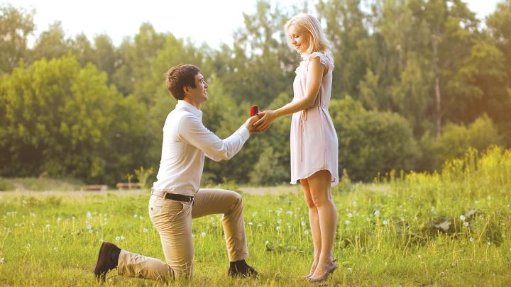 Ein Mann kniet vor einer Frau und macht ihr einen Heiratsantrag.