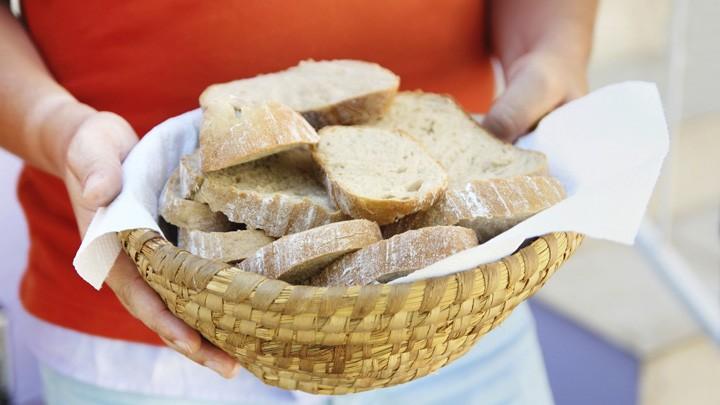 Eine Frau hält einen Korb mit Brot in den Händen.