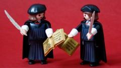 Eine Playmobil-Figur von Martin Luther mit dem Federkiel in rechten Hand steht einer Playmobil-Figur von Martin Luther mit dem Federkiel in der linken Hand gegenüber.