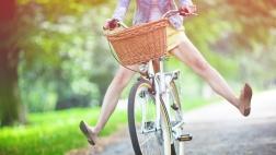Frau streckt auf einem Fahrrad ihre Beine in die Luft.