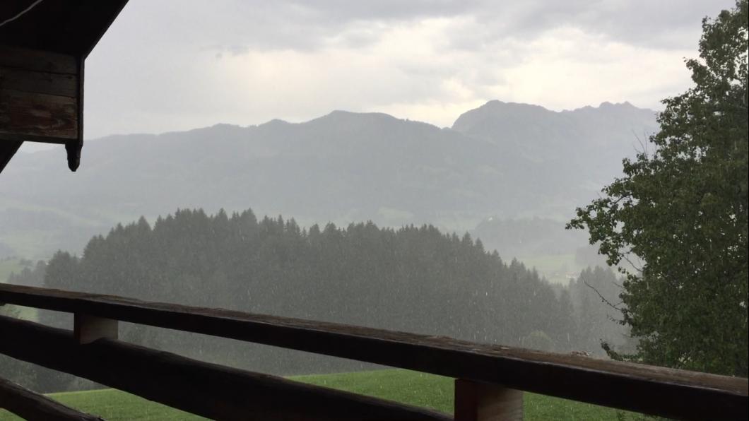 Blick vom Balkon in verregnete Berglandschaft
